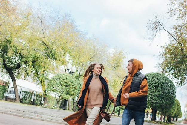 Heureux jeune couple amoureux amis adolescents habillés dans un style décontracté, marchons ensemble dans la rue