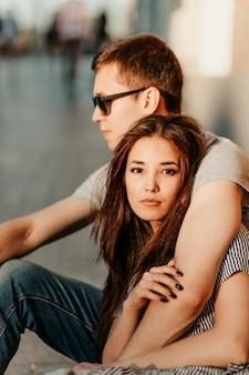 Heureux jeune couple amoureux amis d'adolescents habillés en style décontracté assis ensemble