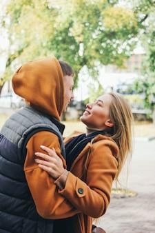 Heureux jeune couple amoureux amis adolescents habillés en style décontracté étreignant rue de la ville en saison froide