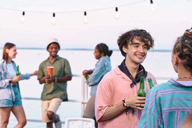 Heureux jeune couple amoureux avec des bouteilles de bière en interaction lors d'une fête en plein air