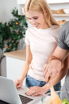 Heureux jeune couple d'amoureux debout à la cuisine