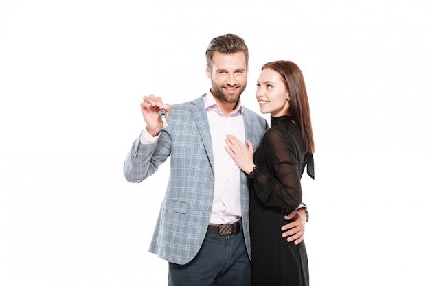 Heureux jeune couple d'amoureux debout isolé tenant les clés.