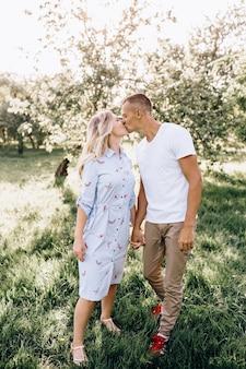 Heureux jeune couple amoureux étreignant jouit de la journée de printemps, aimant sans soucis ensemble à l'extérieur en marchant au parc