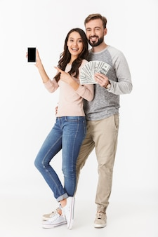 Heureux jeune couple d'amoureux tenant de l'argent montrant l'affichage du téléphone mobile
