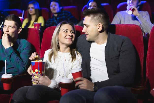 Heureux jeune couple assis au cinéma et aime regarder le film
