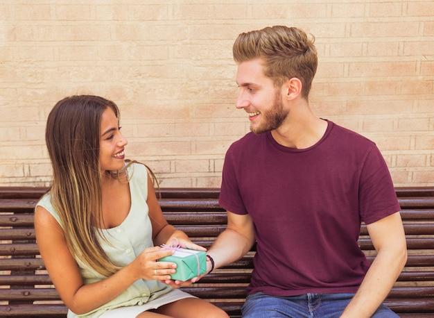 Heureux jeune couple assis sur un banc avec boîte-cadeau