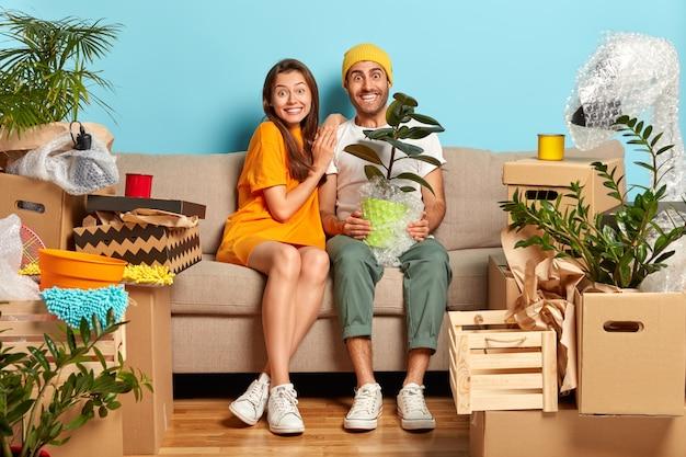 Heureux jeune couple assis sur le canapé entouré de boîtes