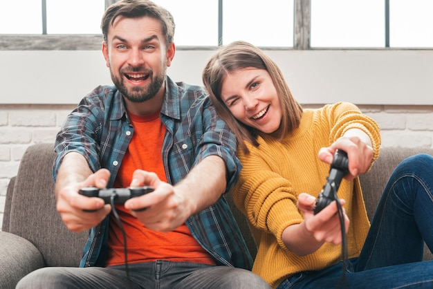 Heureux jeune couple assis sur un canapé s'amuser tout en jouant au jeu vidéo
