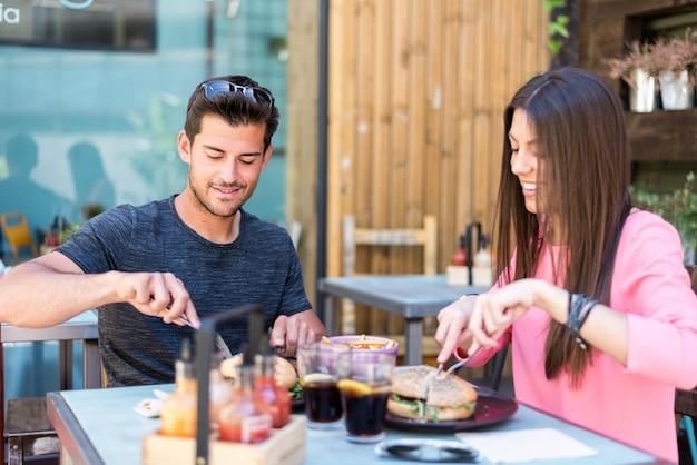 Heureux jeune couple assis dans une terrasse de restaurant mangeant un hamburger