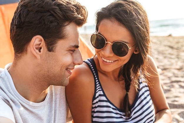 Heureux jeune couple assis ensemble à la plage, camping
