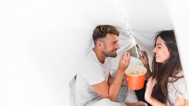 Heureux jeune couple assis à l'intérieur du rideau sur le lit en mangeant des pop-corn