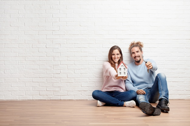 Heureux jeune couple assis sur le sol de leur nouvelle maison. conc