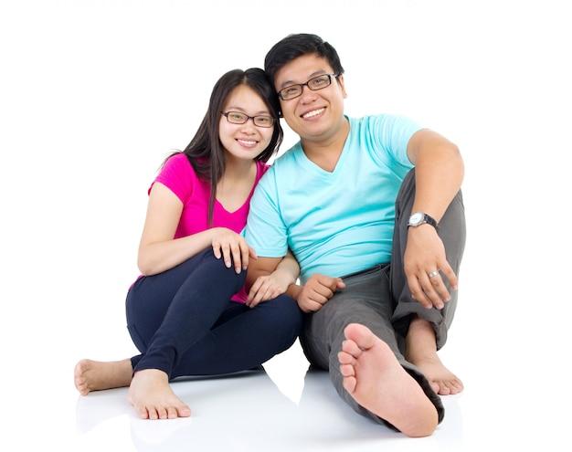 Heureux jeune couple assis sur le sol