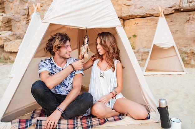 Heureux jeune couple assis et souriant dans un wigwam sur la plage