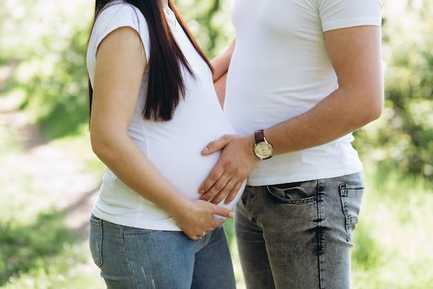 Heureux jeune couple attend bébé dans le parc de l'été