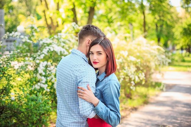 Heureux jeune couple au parc debout et rire sur la belle journée ensoleillée