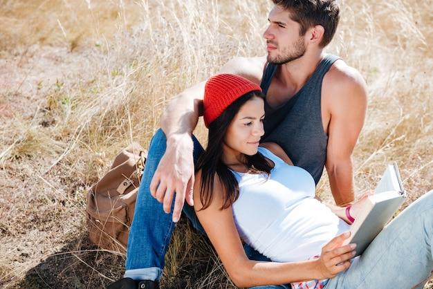 Heureux jeune couple au repos à l'extérieur et livre de lecture