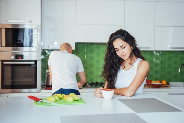 Heureux jeune couple ayant un café dans la cuisine