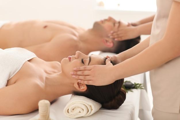 Heureux jeune couple ayant un massage dans un salon de spa