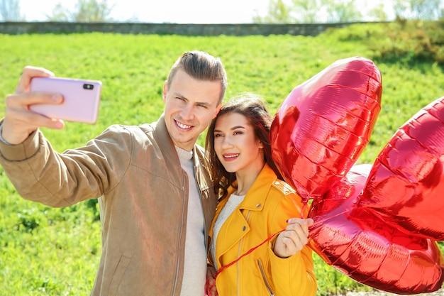 Heureux jeune couple avec des ballons à air en forme de coeur prenant selfie à l'extérieur