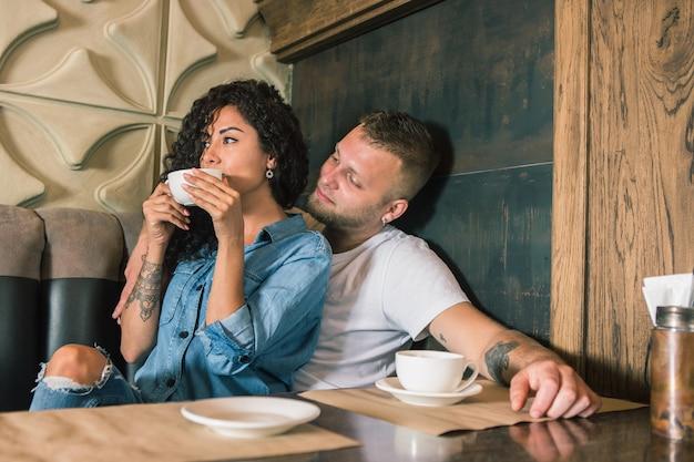 Heureux jeune couple boit du café et souriant alors qu'il était assis au café
