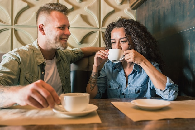 Heureux jeune couple boit du café et souriant tout en étant assis au café