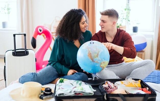 Heureux jeune couple avec carte d'emballage pour des vacances à la maison, nouvelle normalité.