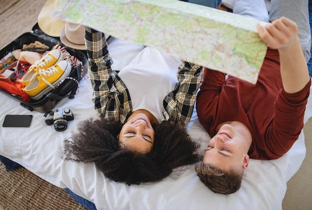 Heureux jeune couple avec carte d'emballage pour des vacances à la maison.