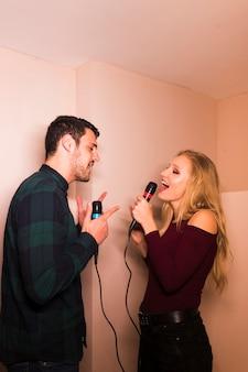 Heureux jeune couple chantant dans le microphone
