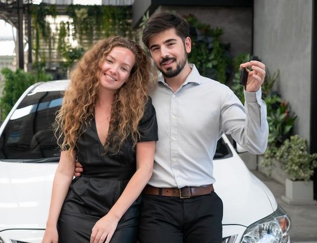 Heureux jeune couple charmant dans des vêtements décontractés étreignant et montrant la clé de la voiture