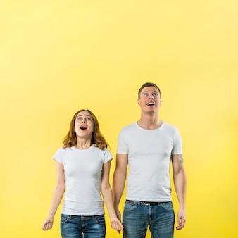 Heureux jeune couple cherchant sur fond jaune