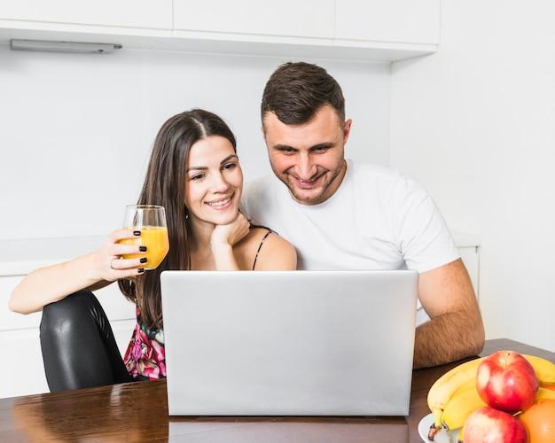 Heureux jeune couple cherche un ordinateur portable dans la cuisine