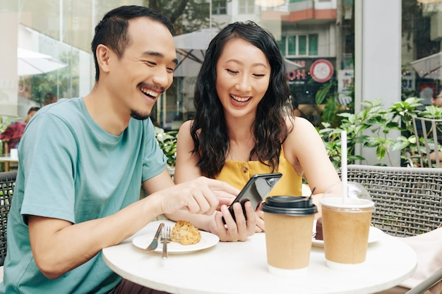Heureux jeune couple chinois regardant des mèmes et des vidéos drôles sur un smartphone lorsqu'il est assis dans un café