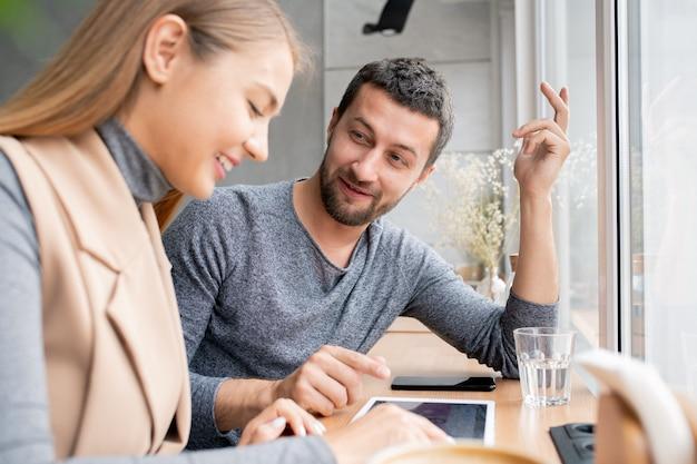 Heureux jeune couple choisir des produits dans la boutique en ligne et discuter des prix tout en passant du temps au café