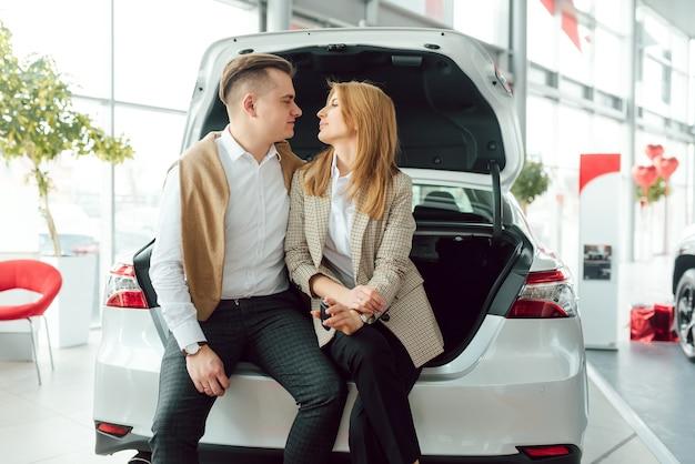 Heureux jeune couple choisit et achète une nouvelle voiture pour la famille chez le concessionnaire.