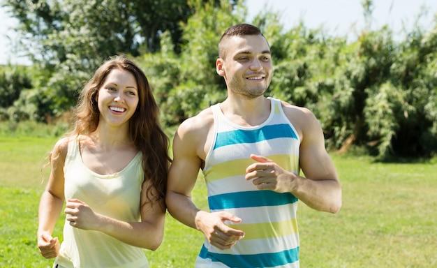 Heureux jeune couple courir en plein air