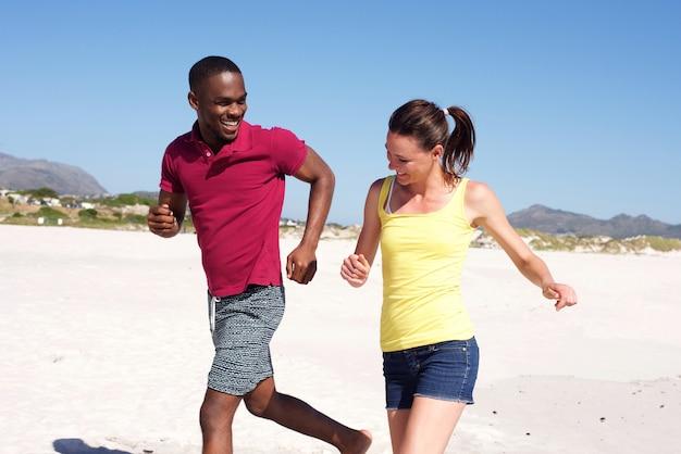 Heureux jeune couple en cours d'exécution sur la plage