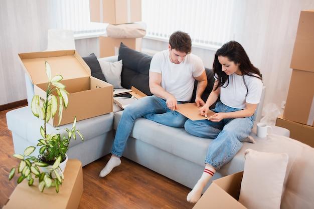 Heureux jeune couple déballant ou emballant des boîtes et emménageant dans une nouvelle maison.