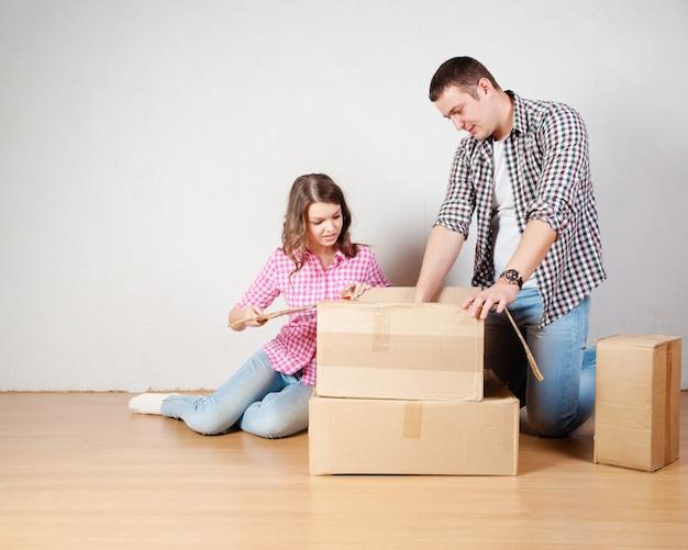Heureux jeune couple déballant ou emballant des boîtes et s'installant dans une nouvelle maison.