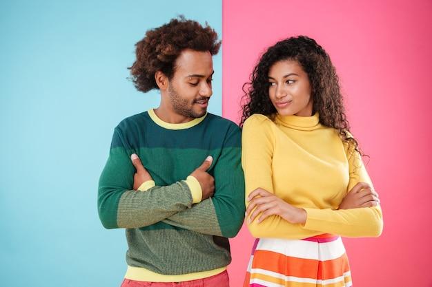 Heureux jeune couple debout avec les bras croisés et se regardant