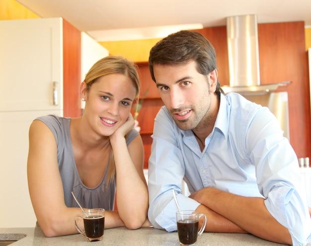 Heureux jeune couple debout dans la cuisine à domicile