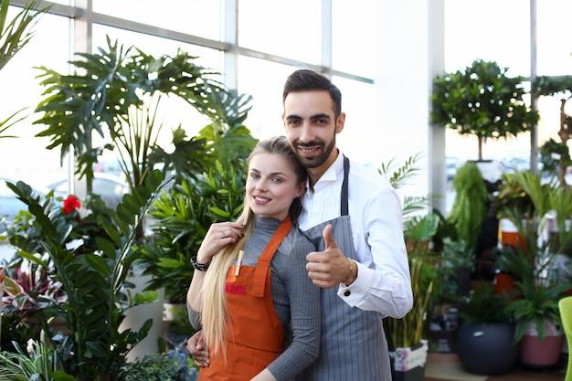 Heureux jeune couple debout dans un magasin de fleurs