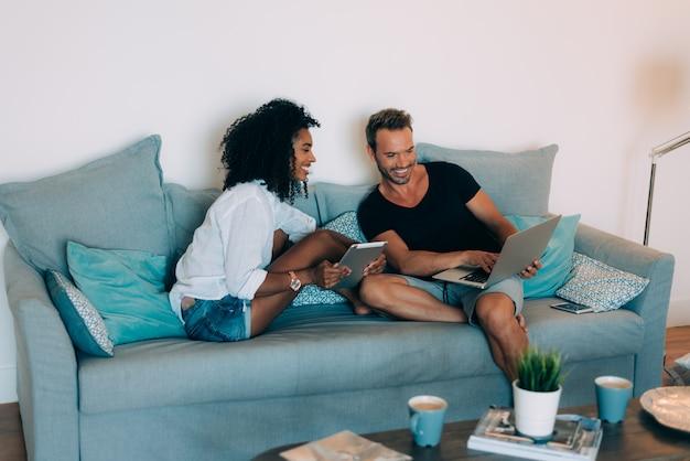 Heureux jeune couple détendu à la maison dans le canapé sur le téléphone mobile et l'ordinateur