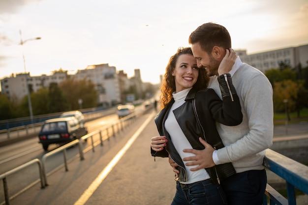 Heureux jeune couple embrassant en riant à la date. les gens embrassent le concept amusant de bonheur.