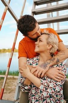 Heureux jeune couple étreignant et riant à l'extérieur dans les escaliers