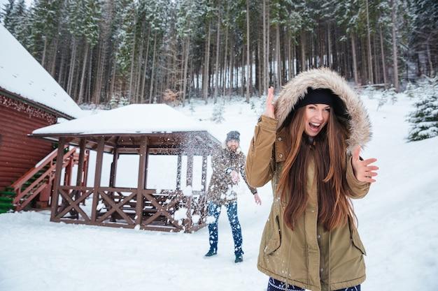 Heureux jeune couple excité jouant aux boules de neige et criant près de la maison dans la forêt d'hiver