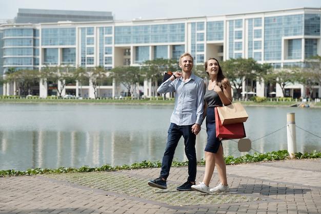 Heureux jeune couple excité se tenant la main en marchant autour de l'étang après avoir fait du shopping dans un centre commercial ou une boutique