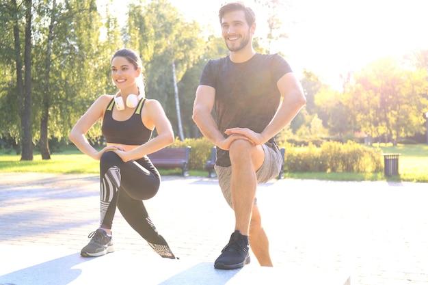 Heureux jeune couple exerçant ensemble dans un parc.