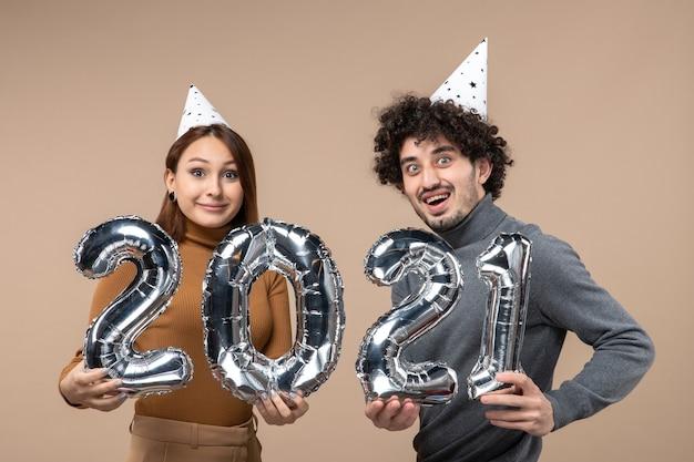 Heureux jeune couple avec une expression faciale surprise avec chapeau de nouvel an pose pour caméra fille montrant et et mec avec et sur gris