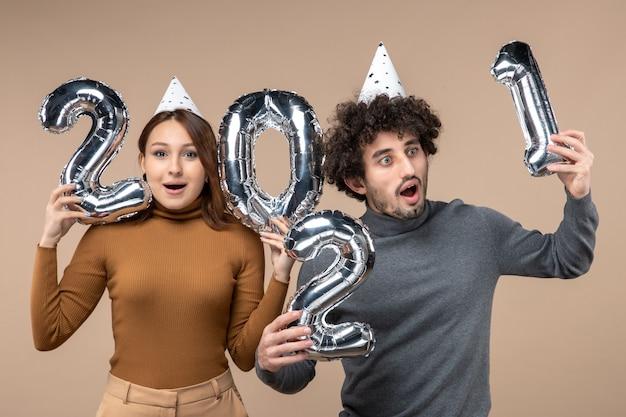 Heureux jeune couple avec une expression faciale surprise porter chapeau de nouvel an pose pour caméra fille montrant et et mec avec et sur gris